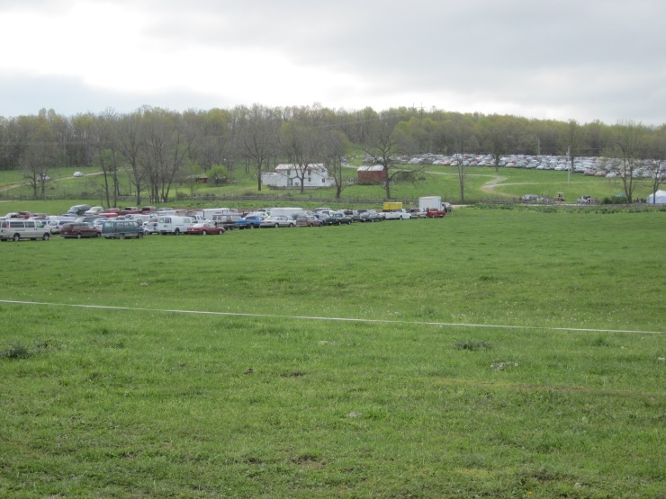 Vendor vehicles in foreground to left, cars of all the visitors up on the hill